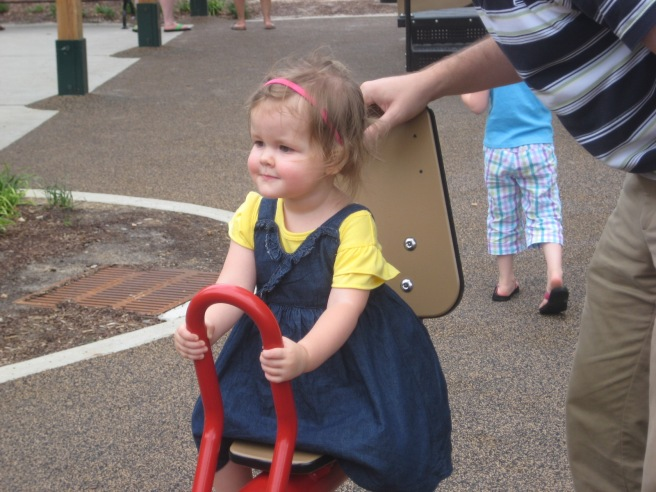 Gracie riding a seesaw on her second birthday