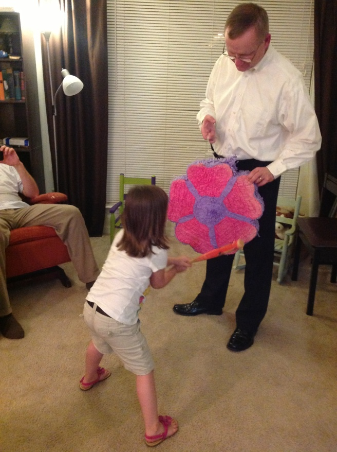 And ladies and gentleman, it's piñata time! (Ok, the girls actually beat on it for an hour in the afternoon. Then beat on it for awhile in the evening; Daddy had to finish it off. = )